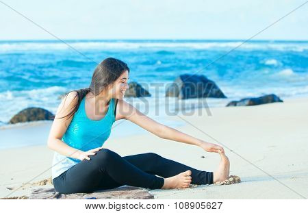 Biracial Teen Girl Stretching And Exercising On Beach