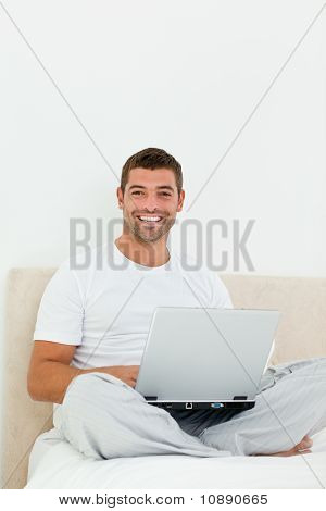 Cheerful Man Working On His Laptop Sitting On His Bed