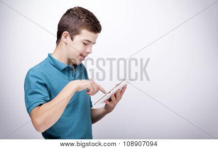 Boy with a digital tablet on grey background