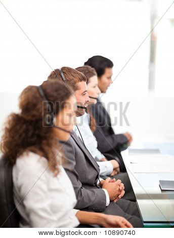 Four Businesspeople On The Phone Sitting At Their Desk