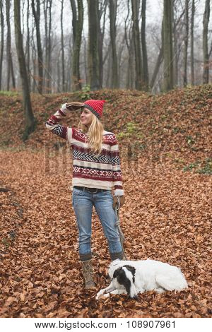 Young blonde woman wearing warm clothes outdoor with her Borzoi dog in autumn forest