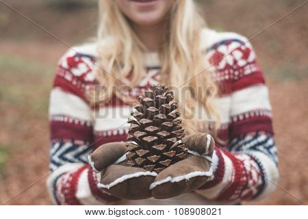 Blonde woman holding pine-cone outdoor in the forest