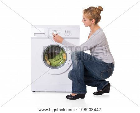 Woman Crouching While Using Washing Machine