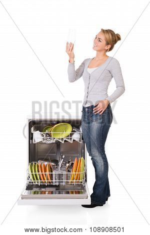 Woman Looking At Clean Glass While Standing By Dishwasher