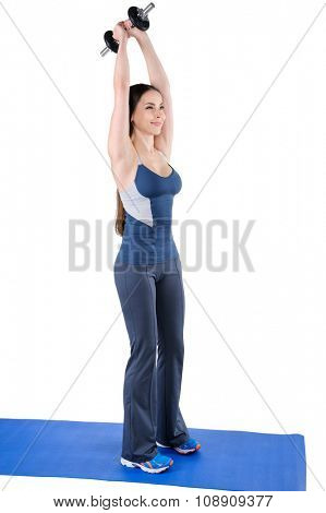 Young woman shows finishing position of Standing Triceps Extension Dumbbell behind head workout, isolated on white