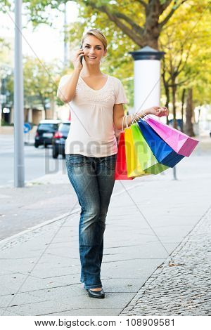Woman Using Mobile Phone While Carrying Shopping Bags