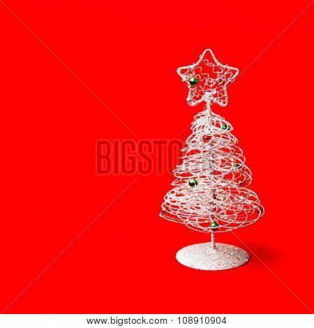 Small tabletop Christmas tree on red background