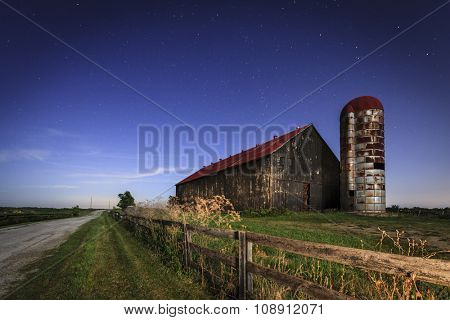 Old farm barn and a country road in moonlight