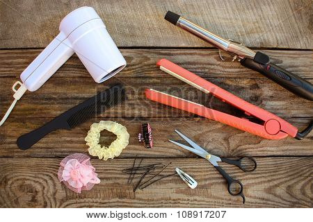Hair accessories: hair dryer, curling iron, hair iron, comb, scissors, hair clips on the old wooden
