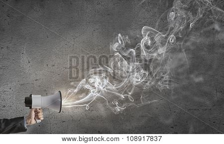 Male hand holding megaphone on cement background