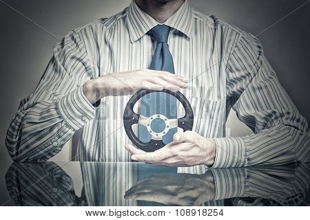Hands of businessman holding with care car steering wheel