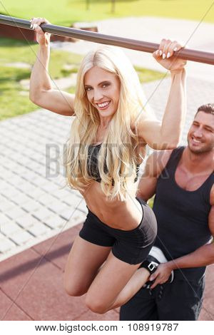 Blonde Woman Pull Up On Bar Trainer Helps