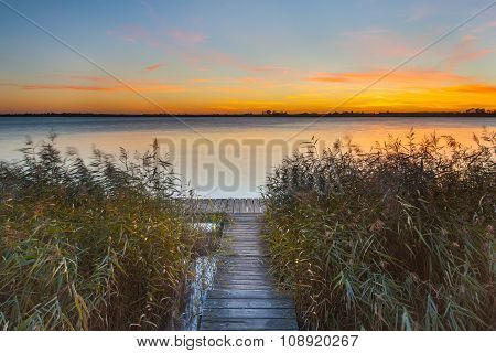Orange Sunset Over Jetty On The Shore Of A Lake