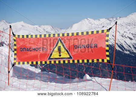 Avalanche danger sign in snow, winter mountain ski resort