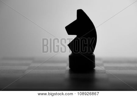 wooden chess board and chess piece black silhouette
