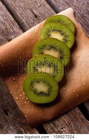 Few Slices Of Kiwi On Peper With Drops
