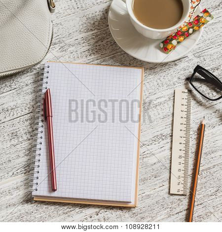 Open A Blank White Notebook, Pen, Women's Bag, Ruler, Pencil And Cup Of Coffee On The White Desk