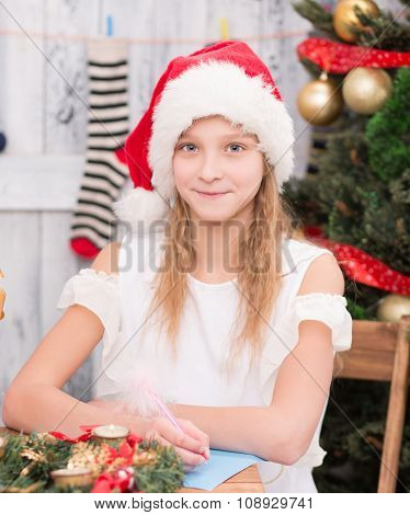 Happy girl sitting at the table and writing New Year and Christmas congratulation in post card