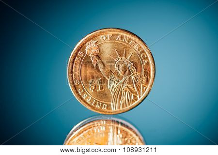 golden dollar coin on blue background