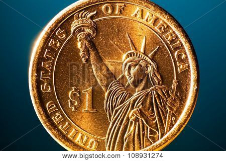 golden dollar coin on blue background, macro view