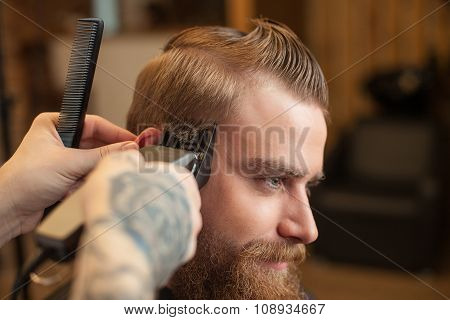 Cheerful bearded guy is getting hairstyle at beauty shop