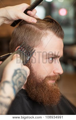 Skillful male barber is working with electric razor