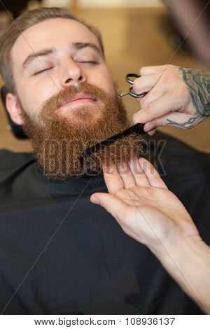 Professional male hairdresser is serving his customer