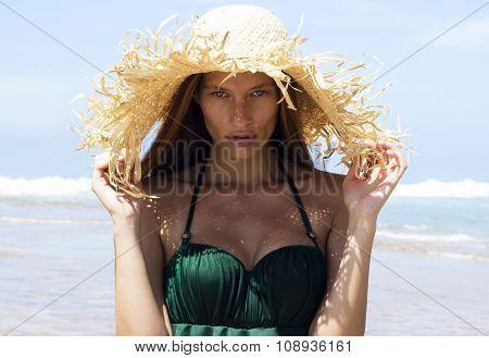 Woman in hat on beach. Beautiful gorgeous girl wearing green bikini poses near sea. Fashion look.Tro