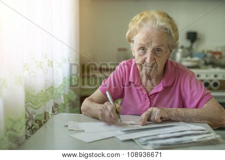 An elderly woman fills out a receipt for payment of utilities, sitting in the kitchen in house.