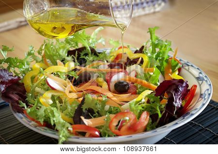 fresh vegetable salad in a bowl with olive oil pouring