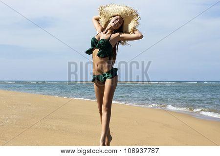 Woman in hat on beach. Beautiful smiling girl wearing green bikini poses jumping near sea. Fashion l