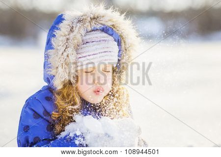 Little Girl Blows Snow With Mittens, On A Snowflakes Bokeh Background .