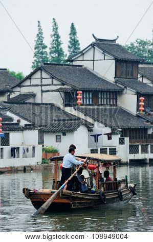 SHANGHAI, CHINA - JUNE 1: Boat and traditional buidings over river on June 1, 2012 in Zhujiajiao, Shanghai. Chinese traditions are well kept in the town attracting thousands of visitors daily.