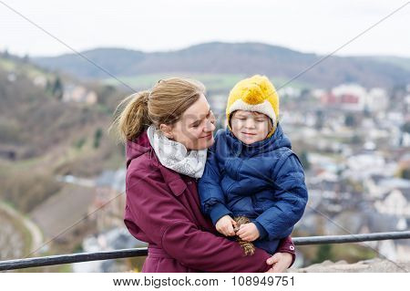 little child and young mother enjoying view city from above