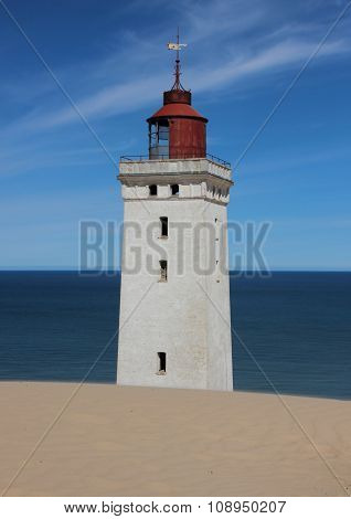 Lighthouse With Sand Dune And Blue Ocean In Horizon