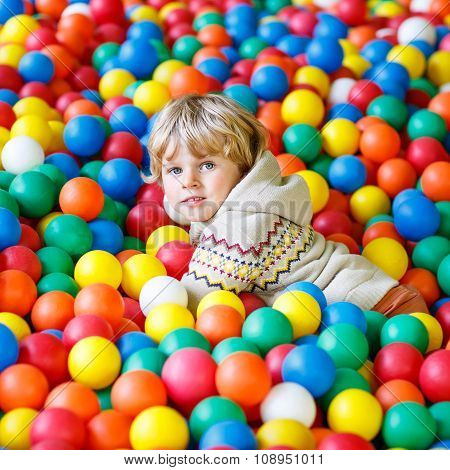child playing at colorful plastic balls playground