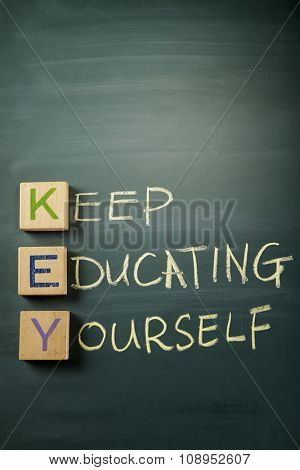 KEEP EDUCATING YOURSELF. Educational concept with wood block and chalk handwriting on a blackboard.