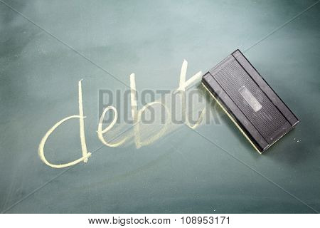 word DEBT written in chalk on a blackboard being rubbed out by an eraser