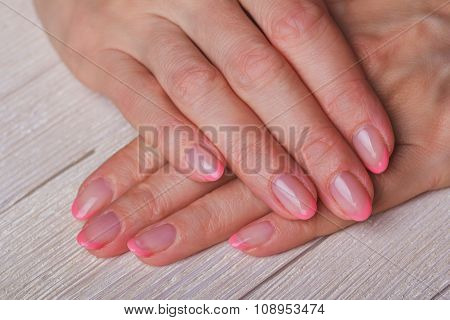 French Nail Art In Light Pink Colour On Wooden Background