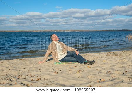 Attractive  Man, Wearing Casually,sitting On The Coast, Looking At The Sky,dreaming, Relaxing And En