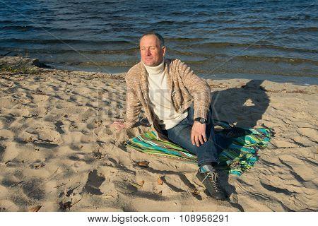 Joyful Smiling Man sitting On The Coast, Looking At The Sun