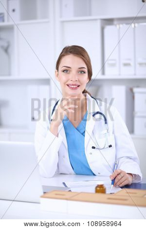 Beautiful young smiling female doctor sitting at the desk and w
