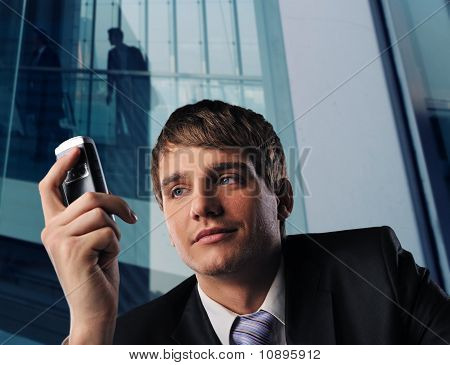 Businessman with mobile phone in front of modern office building
