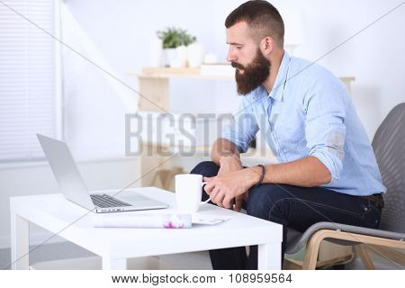 Young man sitting with  laptop and a tea cup at home