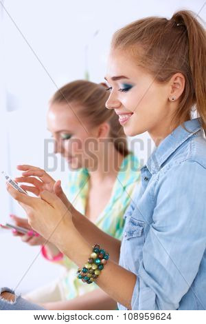Two beautiful women sending messages with mobile, sitting