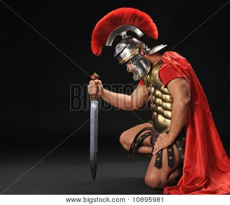 Portrait of a legionary soldier standing on his knee