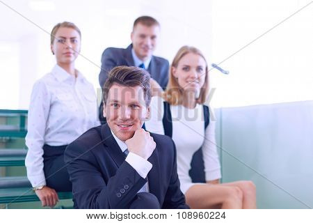 Business people sitting on the ladder in office
