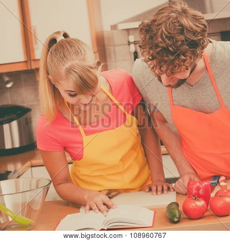 Couple Cooking In Kitchen Reading Cookbook
