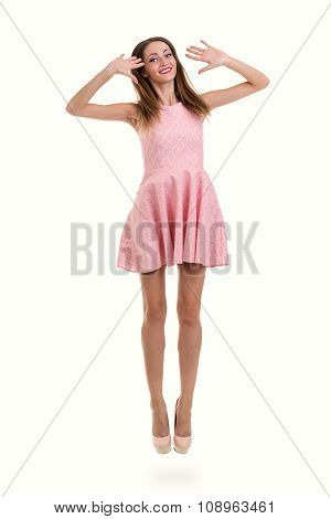 Full length of sensual woman in short dress jumping against isolated white