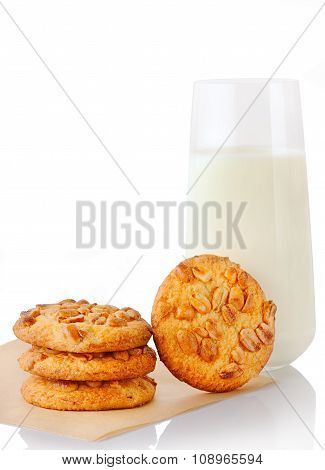 Stack of three homemade peanut butter cookies on baking paper single cookie and glass of milk